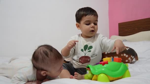 Toddler and 2 months old baby together on the bed, Toddler playing with educational toy turtle, baby turning on the side