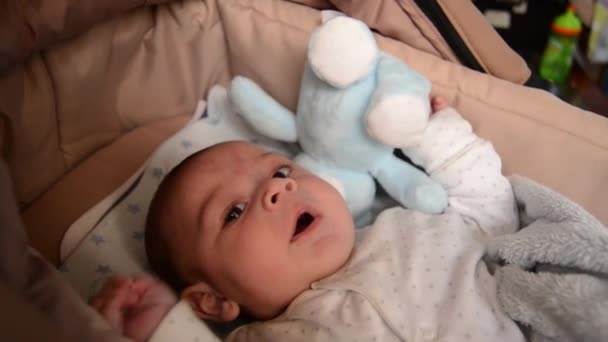 cute 3 months old baby boy making funny faces in baby carry cot
