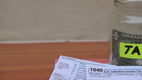 sklenice s DPH štítku jeden dolar poznámku a 1040 formulář na větru - paning vpravo