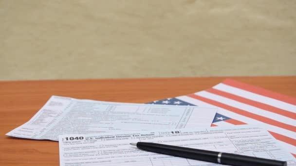 žena uvedení sklenice s daní label a dolar poznámku o formulář 1040 nad Usa vlajka a pera na dřevěné desce stolu statické střílet - duben daně den.