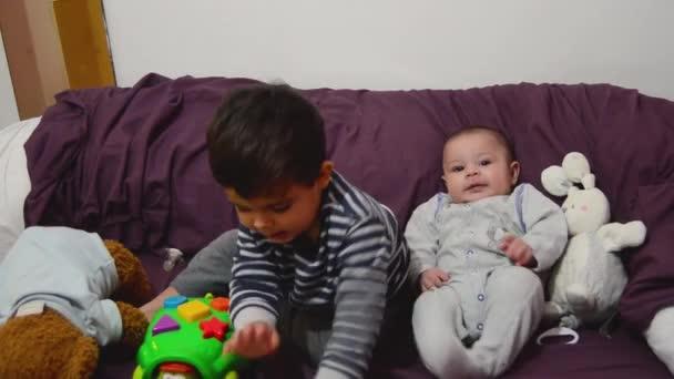 roztomilý dva roky starý chlapec hraje s želva vzdělávací hračka, zatímco jeho bratříček je sledoval a usmíval se