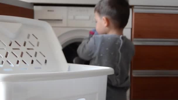 Aranyos két éves fiú pizsama segítve a mosoda, amivel a cipő a mosógép. Fókuszban a mosoda kosár, míg a fiú és a mosógép elmosódnak