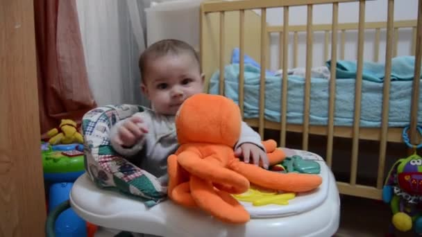 Cute six months old baby boy in the walker holding orange octopus toy and learning to walk
