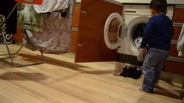Cute two years old boy taking out washed clothes from washing machine and giving it to his mother
