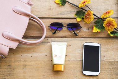 sunscreen spf50 health care for skin face with sunglasses ,pink hand bag ,mobile phone of lifestyle woman relax summer arrangement flat lay style on background wooden