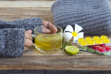 hand of woman holding herbal healthy drinks hot honey lemon and lozenge for health care sore throat with knitting wool scarf of lifestyle woman relax in winter season on table