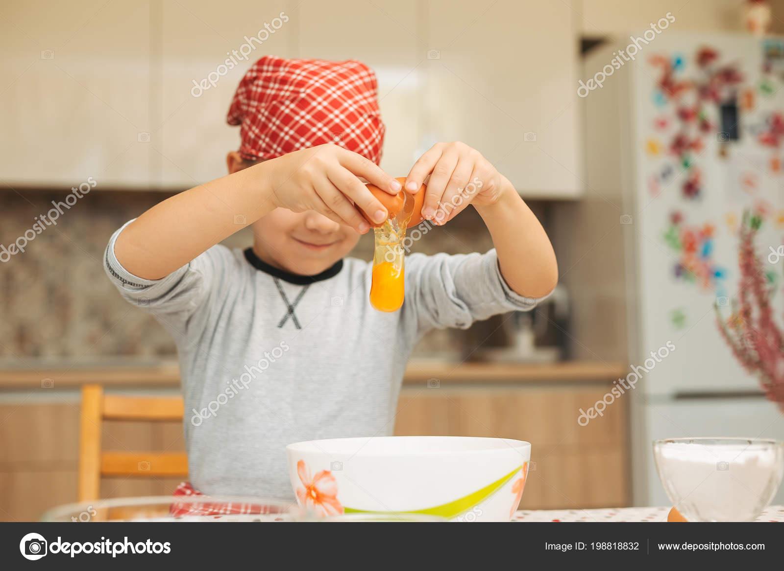 Petit garçon de cuisine. Œuf de rupture enfant dans bol ...