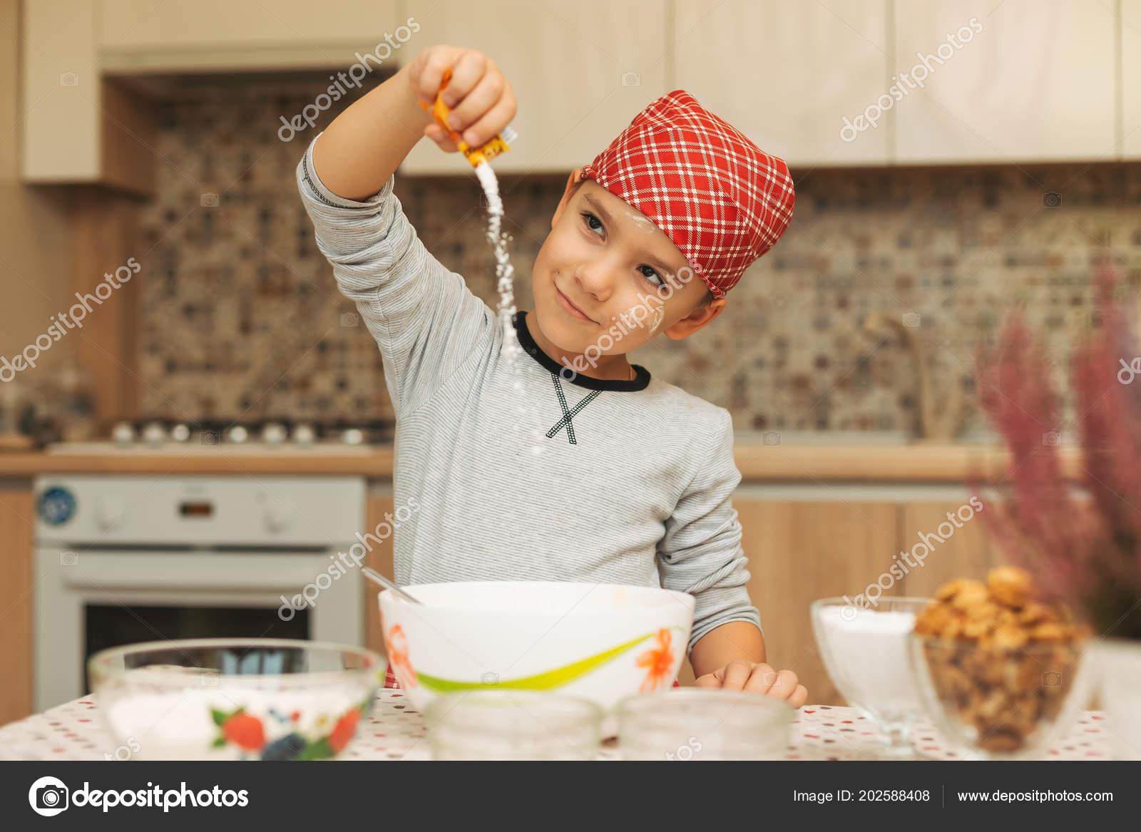 Sara Cucina Biscotti Di Natale.Ragazzo Versando La Polvere Magica Mentre Cuociono I Biscotti Di