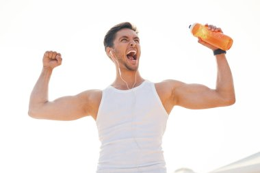 Athletic muscular man feeling victory and enjoys success holding a bottle of water. Emotion, power, gesture - young man celebrating victory and screaming with sun light in background.