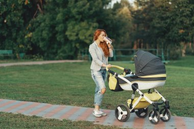 A young mother enjoying the park walk in the morning, drinking a hot tea, with her little child relaxing in his baby trolley.
