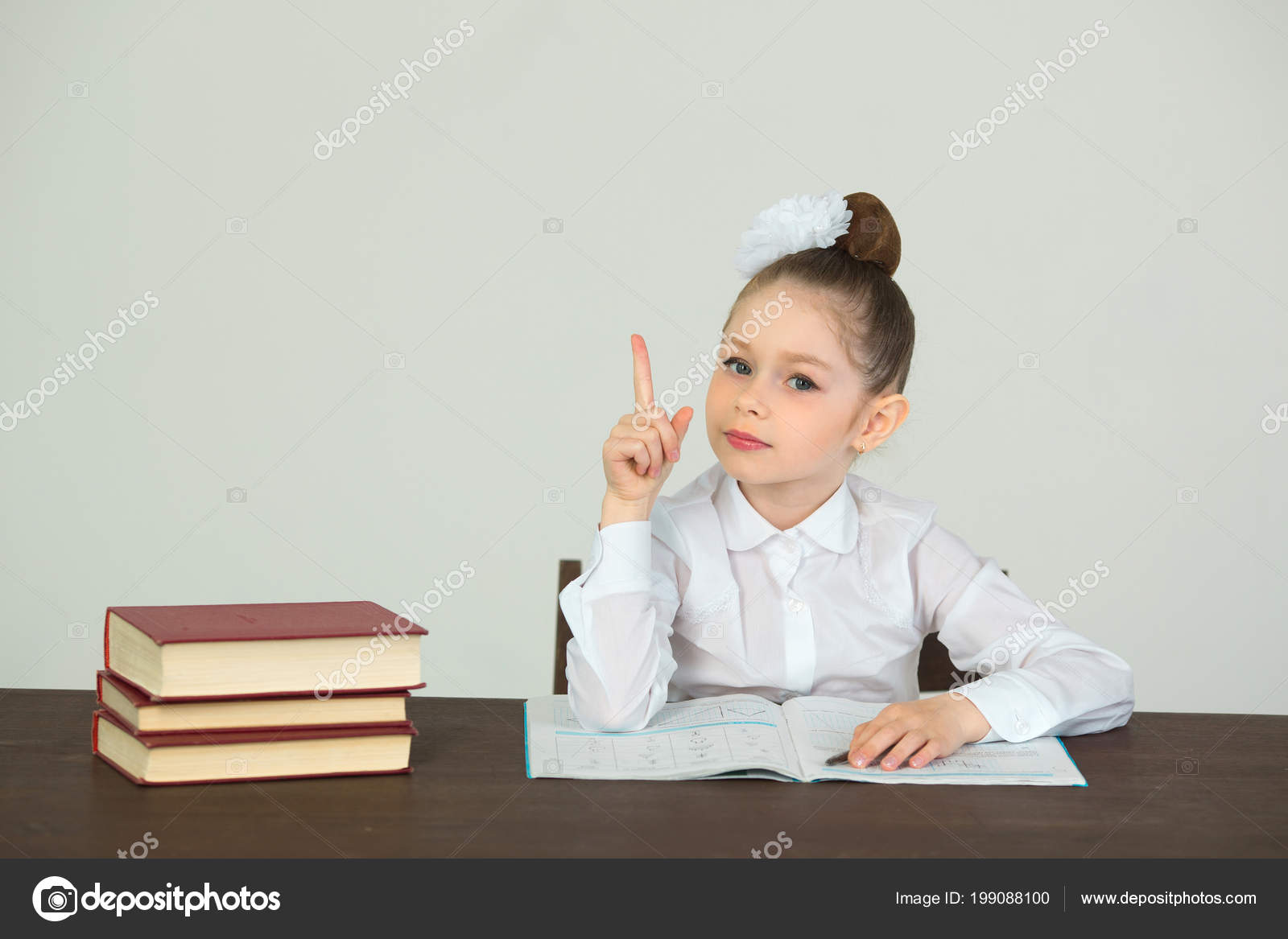 Belle petite fille avec archet sur tête assis bureau avec