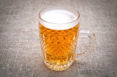 Glass of frothy light beer on the burlap cloth background.