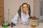 Emotional student girl on chemistry lesson. Pharmacist or apothecary woman. Scientific experiment background. Young intern in chemical laboratory concept.