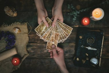 Tarot cards, magic book and fortune teller hands on a wooden table background. Future reading concept. Divination.