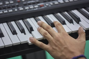 Hand of a musician pressing the keys of an electronic keyboard while playing at a concert