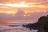 Fotografie Colourful sunrise with surfers standing on rocks at Burleigh Heads, Gold Coast Australia Australia