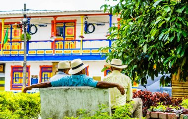 People of Colombia, group of old man sitting on bench in the colorful streets of Filandia Village