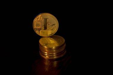 Kripto curency litecoin altın sikkeleri üzerinde siyah bir arka plan. Yalancı sikke ek olarak, orada duran litecoin.