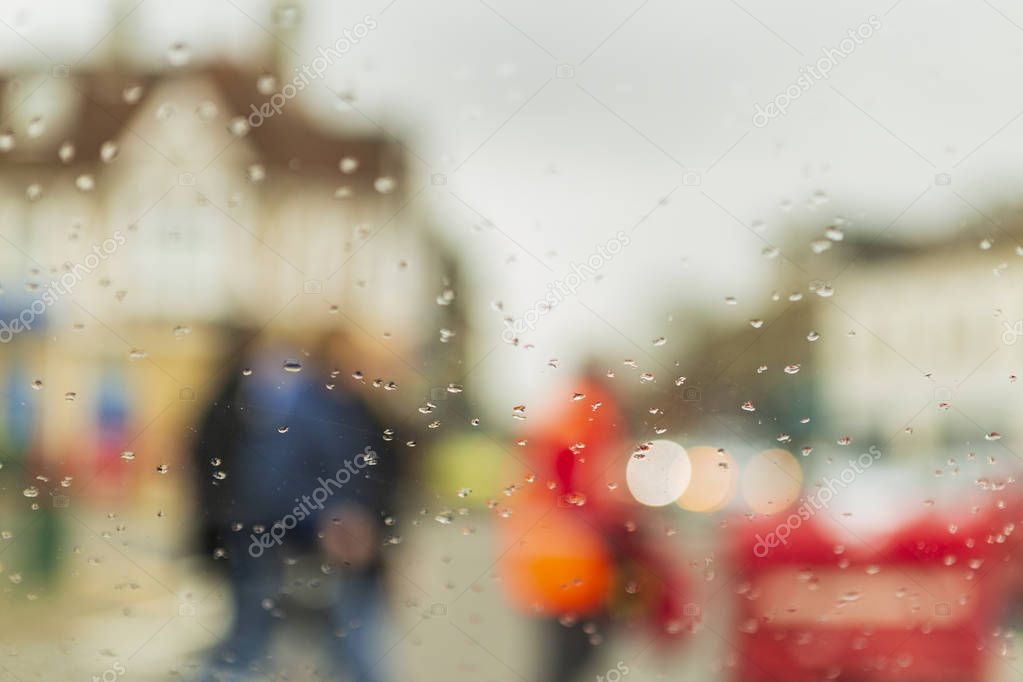 rain drops on the window of a car and smudged cars and people and pedestrians. raindrops in focus and blurred background.