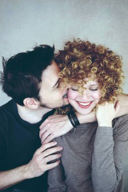 photo of young cute woman with curly hair hug with man on grey wall background