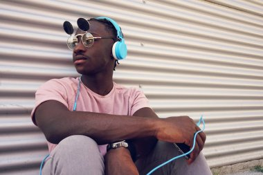 Young handsome  man wearing funny sunglasses listening to music with his smartphone