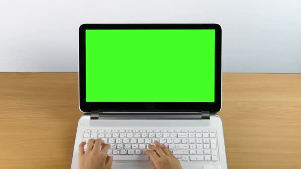 Typing on a laptop computer, with green screen monitor for advertising.