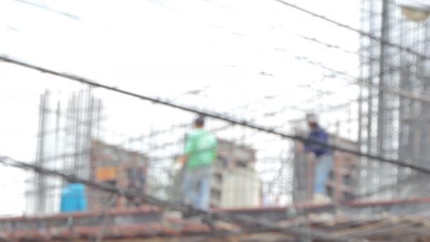 Rozmazané záběry stavební dělníci budují, obytné budovy ve městě.