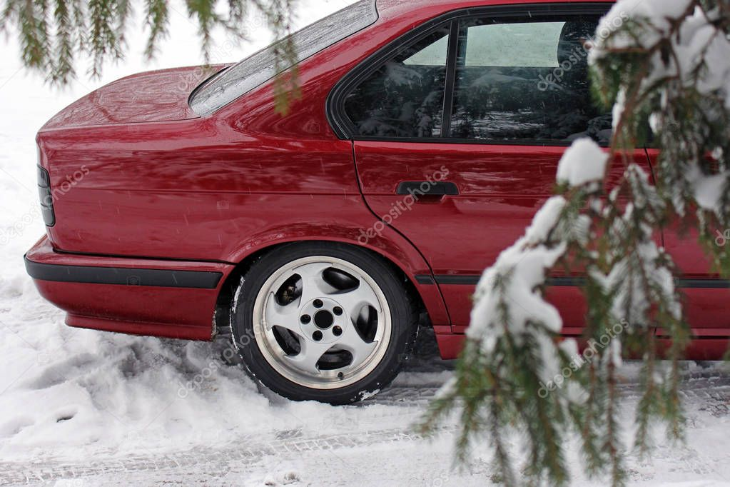 Part of a red car in the woods in winter