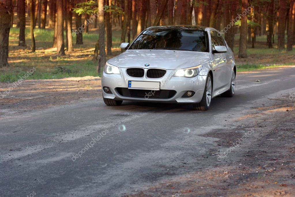 Kiev, Ukraine - September 9, 2018. BMW E60 on the forest road. Car in the forest