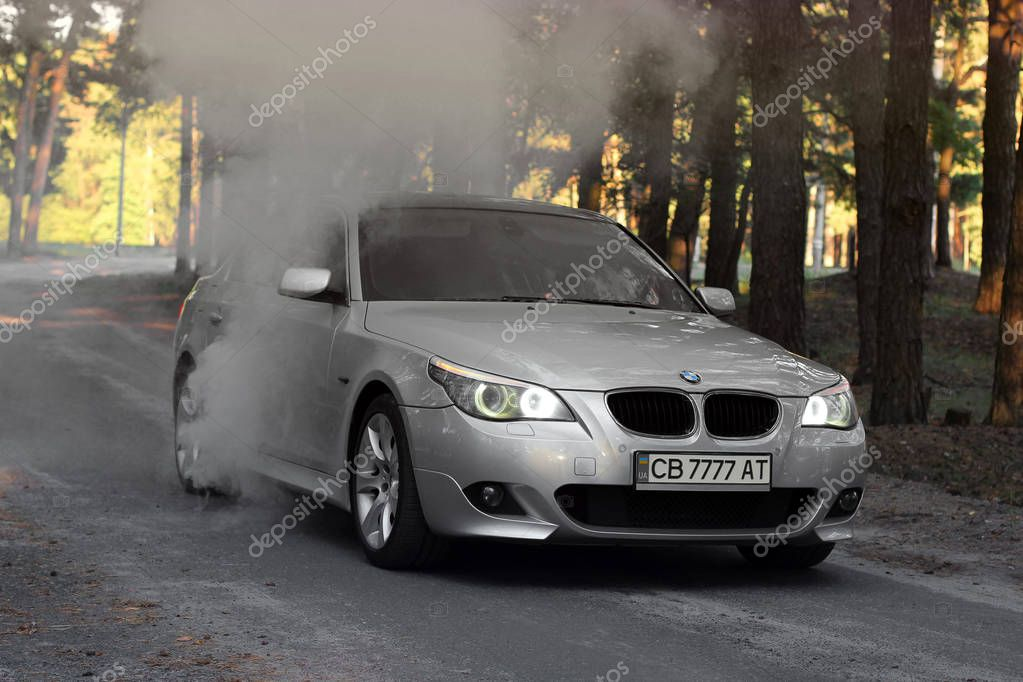 Kiev, Ukraine - September 9, 2018. BMW E60 on the forest road. Car and smoke