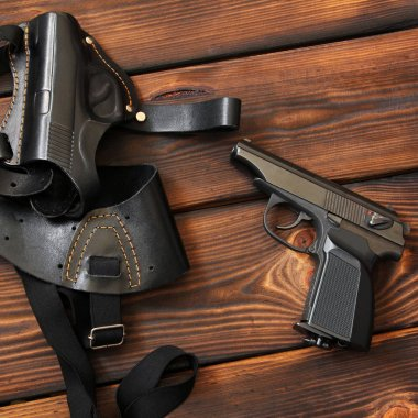The gun and holster for a handgun on wooden background. Weapon