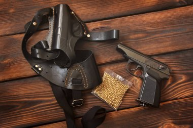 Weapon. The gun and holster for a handgun on wooden background
