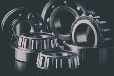 Close-up of a set of ball and roller bearings for repair lying on the desktop in the dark. Can be used as a background