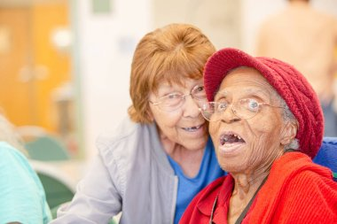 Hispanic and  African American women together in a senior center