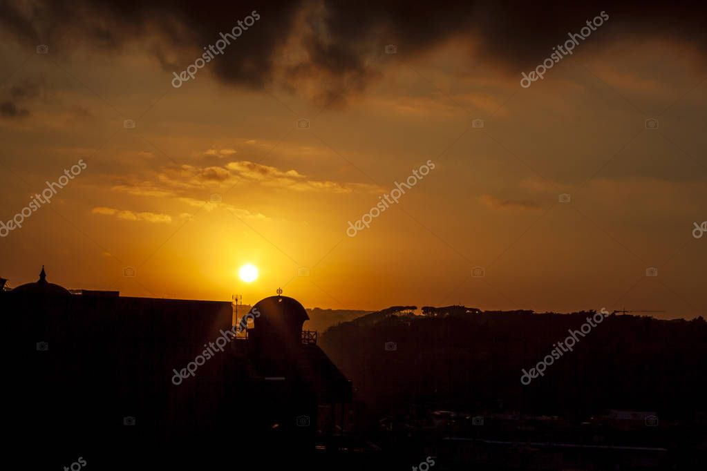 A picture take during summer sunset in one of Rome neighborhood suburbs. Black silhouette of cityscape.
