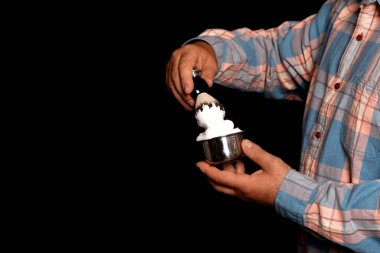 man holding bowl with foam and brush in hands  for shaving  on black background