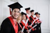 Fotografie Student bakalářského roucho s diplomem doma. Závěrečný den