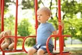 Fotografie Niedlichen kleinen Jungen spielen auf Schaukeln im park