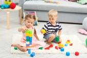 Fotografie Roztomilé děti si hrají s konstruktor na podlahu doma