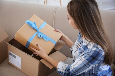 Young woman opening parcel at home