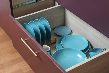 Different tableware in drawer on kitchen