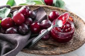 Photo Glass jar with delicious plum jam on plate