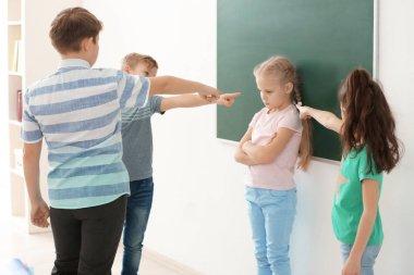 Children bullying their classmate in school