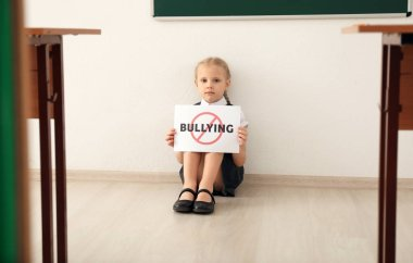 Little girl sitting on floor and holding sign with crossed word