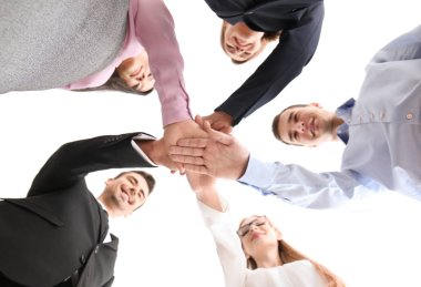 People putting hands together against white background, view from below. Unity concept