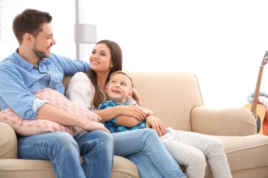 Happy family resting together on sofa at home