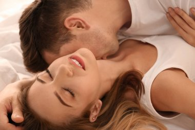Beautiful young couple being intimate in bed at home