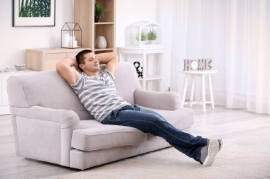 Young man relaxing on sofa at home stock vector