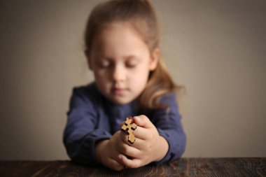 Religious Christian girl praying at table, closeup