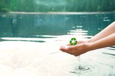 Woman holding water in hands over lake. Recycling concept. Save nature and environment